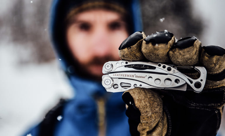 Leatherman stainless steel skeletool multi-tool in hand, used outdoors in snow
