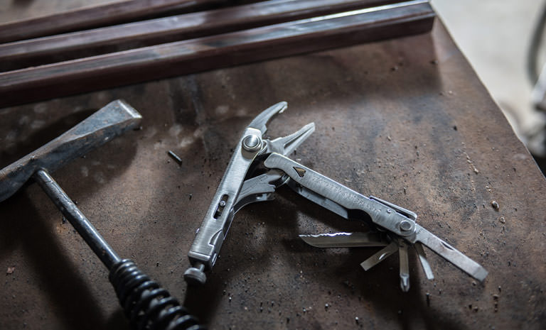 Leatherman crunch multi-tool next to hammer, stainless steel, open view