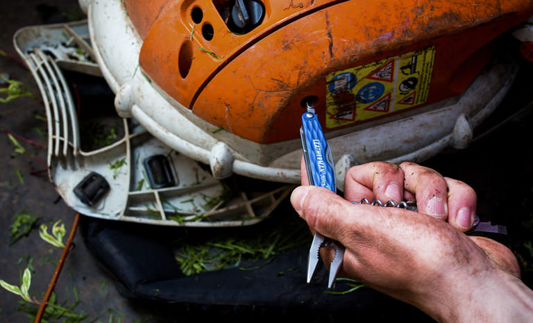 Leatherman blue juice cs4 multi-tool outdoors in hand, fixing a machine